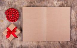 Abra el diario con las páginas en blanco del papel reciclado, de la caja de regalo con un arco y de un collar coralino Copie el e Fotografía de archivo
