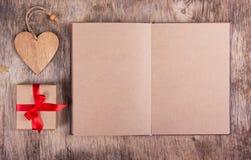Abra el diario con las páginas en blanco del papel reciclado, de la caja de regalo con un arco y de un corazón de madera Copie el Imagen de archivo