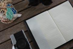 Abra el diario rodeado con los accesorios que viajan Fotografía de archivo