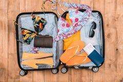 Abra el equipaje por completo de ropa del ` s de la mujer y de otros artículos esenciales de las vacaciones Aliste a las vacacion foto de archivo