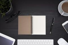 Abra el espiral en blanco del cuaderno sobre la tabla negra del escritorio Imagenes de archivo