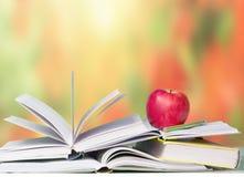 Abra el fondo rojo de educación escolar de la manzana de los libros Imagen de archivo libre de regalías