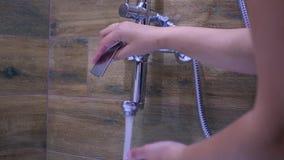 Abra el golpecito de agua en el cuarto de baño y regúlelo, 4k metrajes