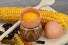 Abra el huevo alrededor de maíz, de pastas y de habas en una tabla de cortar Yema de huevo y albumen fotografía de archivo