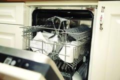 Abra el lavaplatos con los utensilios limpios Fotografía de archivo