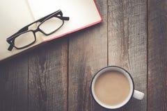Abra el libro con café y vidrios en fondo de madera con la copia Imagen de archivo