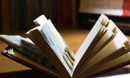 Abra el libro con el dinero Fotos de archivo
