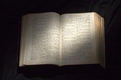 Abra el libro con el proyector ligero en el texto Lectura del libro abierto e Fotografía de archivo libre de regalías