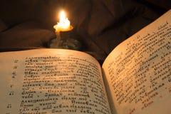 Abra el libro con la luz suave de la vela que vierte en el texto Lectura del ope Foto de archivo libre de regalías