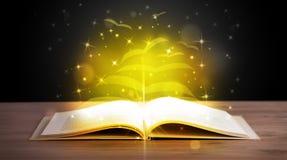 Abra el libro con las páginas del papel del vuelo del resplandor de oro Imagenes de archivo