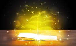 Abra el libro con las páginas del papel del vuelo del resplandor de oro fotos de archivo libres de regalías