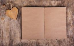 Abra el libro con páginas en blanco y una tarjeta del día de San Valentín de un árbol Cuaderno hecho del papel y de la tarjeta de Fotos de archivo