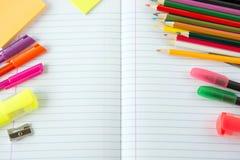 Abra el libro de ejercicio con las plumas y los lápices Imagenes de archivo