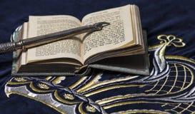 Abra el libro de la biblia en hebreo con la mano punteaguda de plata imagen de archivo