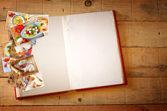 Abra el libro de la receta con las páginas en blanco y el collage de fotos con los diversos platos de la comida Fotografía de archivo
