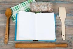 Abra el libro de la receta en el fondo de madera, cuchara, rodillo, mantel a cuadros del verde Foto de archivo libre de regalías
