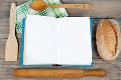 Abra el libro de la receta en el fondo de madera, cuchara, rodillo, mantel a cuadros del verde Imagen de archivo