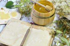 Abra el libro del diario con las flores, la miel y el cazo del tilo en tablones de madera Fotos de archivo
