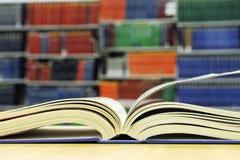 Abra el libro delante del estante Fotografía de archivo