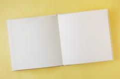 Abra el libro en blanco en fondo amarillo Foto de archivo
