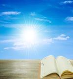 Abra el libro en el cielo azul de madera y de la sol Foto de archivo libre de regalías
