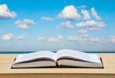 Abra el libro en el escritorio y el mar Fotos de archivo libres de regalías