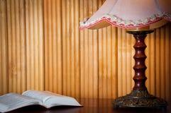 Abra el libro en la tabla y la lámpara vieja del vintage en fondo de madera en casa por la tarde Foto horizontal Espacio para el  Fotos de archivo