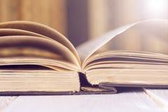 Abra el libro en los tablones de madera sobre fondo ligero abstracto Fotos de archivo libres de regalías