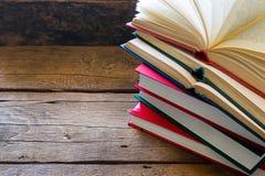 Abra el libro en una pila de libros cerrados Fotos de archivo