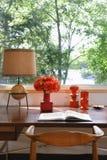 Abra el libro, la lámpara y los ornamentos retros en el escritorio Foto de archivo