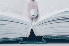 Abra el libro Una pluma miente entre las p?ginas en un libro abierto imagenes de archivo