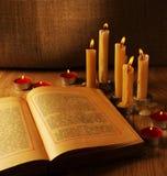 Abra el libro viejo y las velas ardientes Imagen de archivo