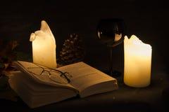 Abra el libro visto por la luz de una vela Imágenes de archivo libres de regalías