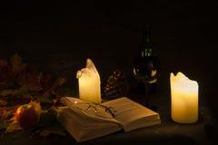 Abra el libro visto por la luz de una vela Foto de archivo