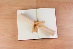 Abra el libro y el diploma Imagen de archivo