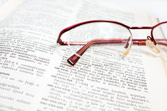 Abra el libro y el vidrio del diccionario Imagen de archivo libre de regalías