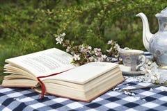 Abra el libro y el viejo juego de té en la tabla Foto de archivo