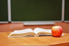 Abra el libro y una manzana en el escritorio en la sala de clase Escuela Fotografía de archivo