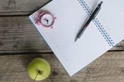 Abra el orden del día del cuaderno con el calendario y el pequeño reloj rosado en el 8:00 Imagenes de archivo