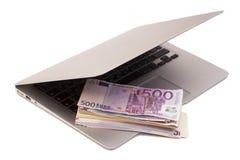 Abra el ordenador portátil con el dinero euro imágenes de archivo libres de regalías