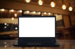 abra el ordenador portátil con la pantalla blanca en la tabla de madera delante del fondo borroso extracto de las luces del resta Fotos de archivo libres de regalías