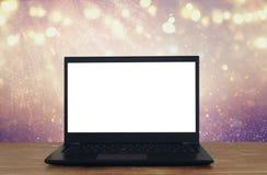 abra el ordenador portátil con la pantalla blanca en la tabla de madera delante del fondo abstracto del brillo imagenes de archivo