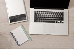 Abra el ordenador portátil, la tableta de gráficos y el cuaderno con el lápiz en una tabla ligera, visión superior Fotografía de archivo