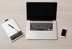 Abra el ordenador portátil, la tableta de gráficos y el teléfono elegante en una tabla ligera Foto de archivo