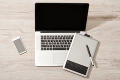 Abra el ordenador portátil, la tableta de gráficos y el teléfono elegante en una tabla ligera, visión superior Fotos de archivo libres de regalías
