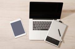Abra el ordenador portátil, la tableta de gráficos y la tableta en una tabla ligera, visión superior Foto de archivo libre de regalías