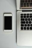 Abra el ordenador portátil y el smartphone en la tabla blanca Imágenes de archivo libres de regalías