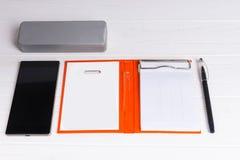 Abra el organizador personal con una pluma, la caja para los vidrios y el móvil Foto de archivo libre de regalías