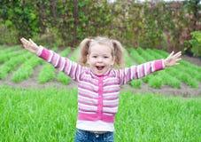 Abra el pequeño prado feliz del verde de la muchacha de los brazos Imagenes de archivo