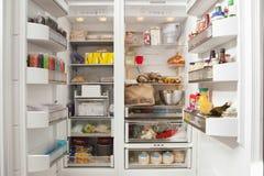 Abra el refrigerador con los productos alimenticios almacenados Foto de archivo libre de regalías